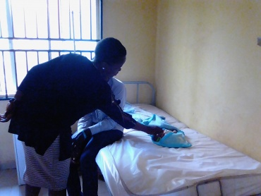 Dr Temitayo Iruobe Examine a new born baby at Ogede Community Primary Health Center (baby's father inset)